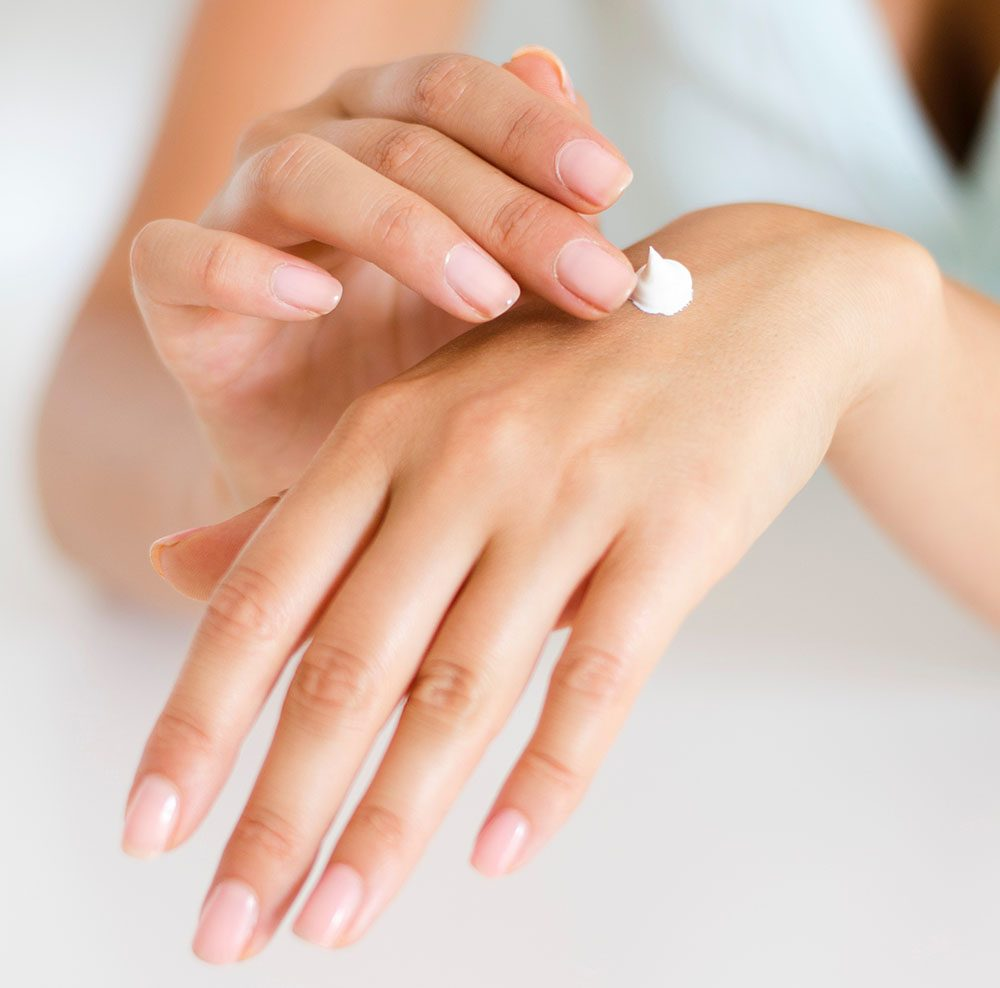 Person applying lotion to hands image
